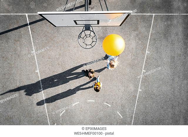 Austria, Aerial view of basketball field, mother and children playing basketball with big ball