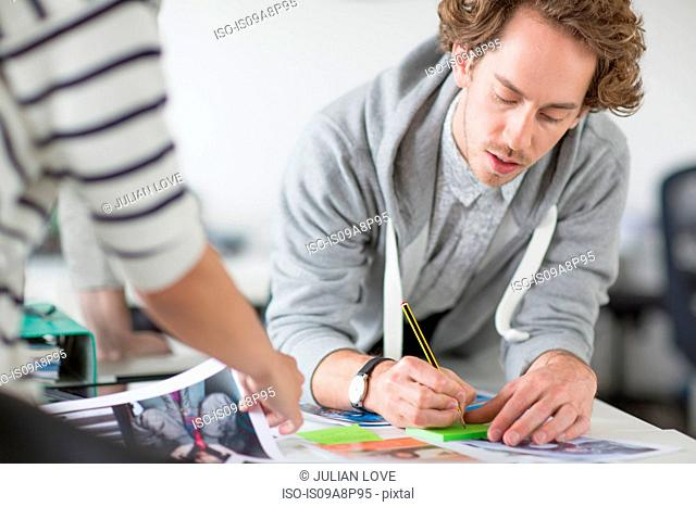 Young man making notes on desk in creative office