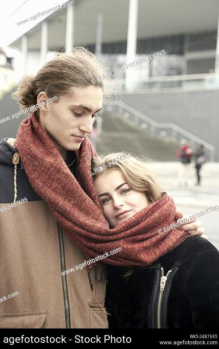 young couple sharing winter scarf