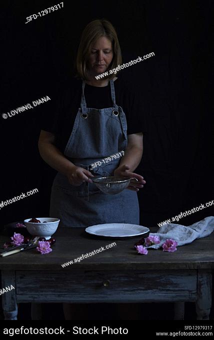 A woman sieves icing sugar over a cake plate