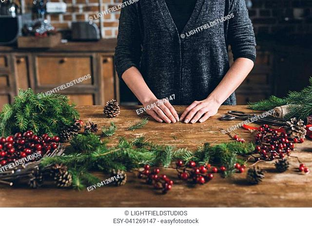 cropped view of florist making Christmas decorations of fir branches, decorative berries and pine cones at workplace