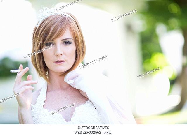 Bride smoking a cigarette before wedding