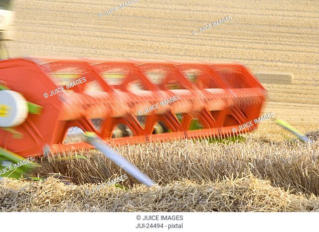 Combine harvesting wheat in rural field