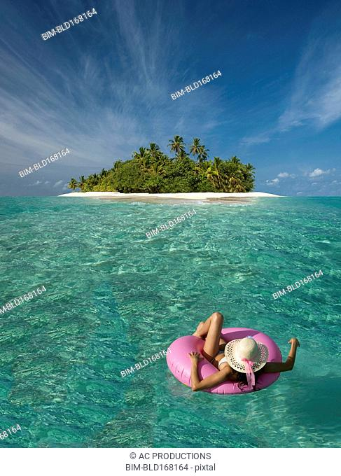 Caucasian woman floating near tropical island