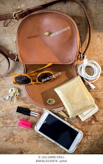 Purse with wall, cell phone, lipstick and sunglasses