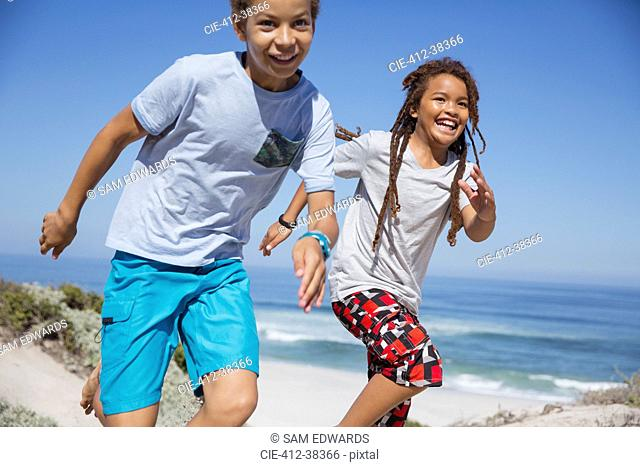 Playful brother and sister running on sunny summer beach