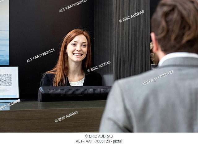 Female receptionist looking at businessman