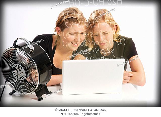 Two teenage girls studying mathematics in front of the laptop