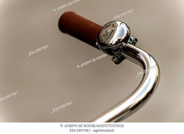 The handle bar of an old style bicycle showing a bell and a plastic hand grip