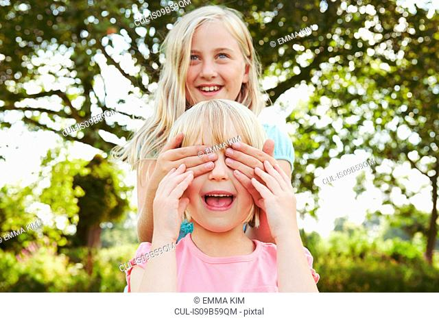 Girl with hands covering friend's eyes in garden
