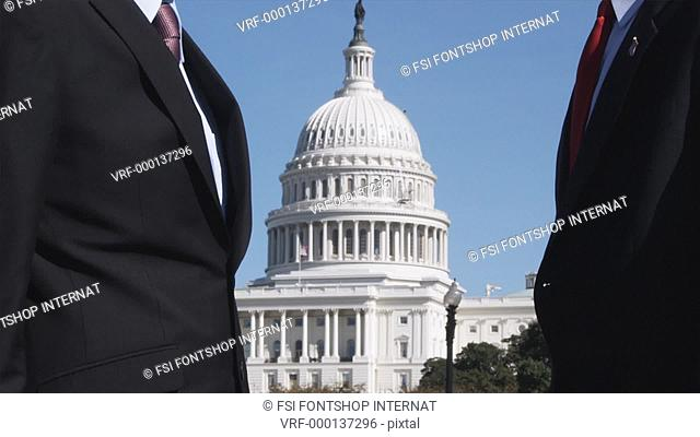 MS of two well-dressed men shaking hands in front of the Capitol Building, Washington DC, USA