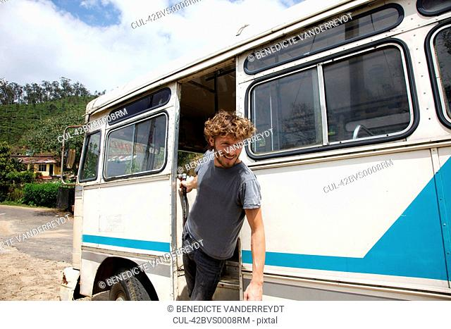 Smiling man leaning out bus door