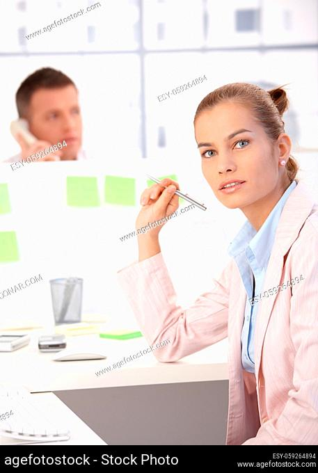 Attractive young girl working in modular office, man in background talking on phone