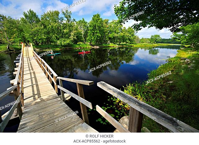 Foot bridge and kayakers on the Mersey River in Kejimkujik National Park and National Historic Site of Canada, Nova Scotia
