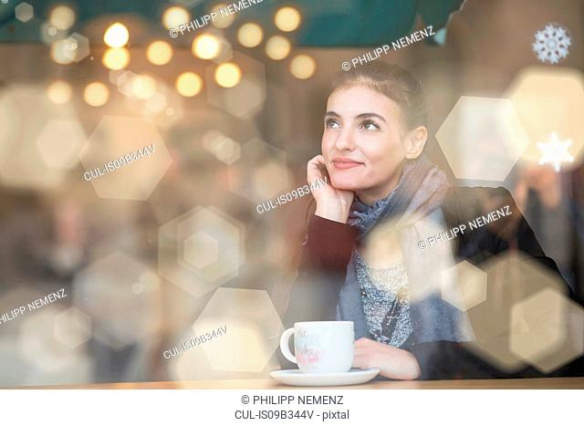Young woman sitting in cafe, looking out of window