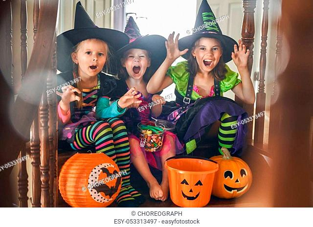 Happy Halloween! Three cute little laughing girls in witches costumes