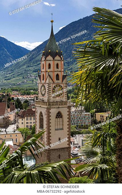 Palms decorate the townscape of Merano with Church of St. Nicholas in South Tirol, seen from the Tappeinerpromenade above the town