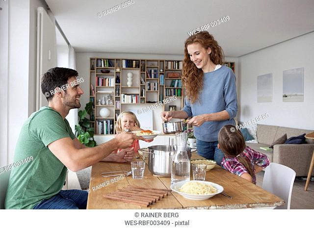 Couple with two children going to have lunch together at home