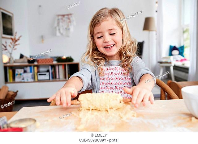 Young girl rolling out cookie dough, dough stuck to rolling pin