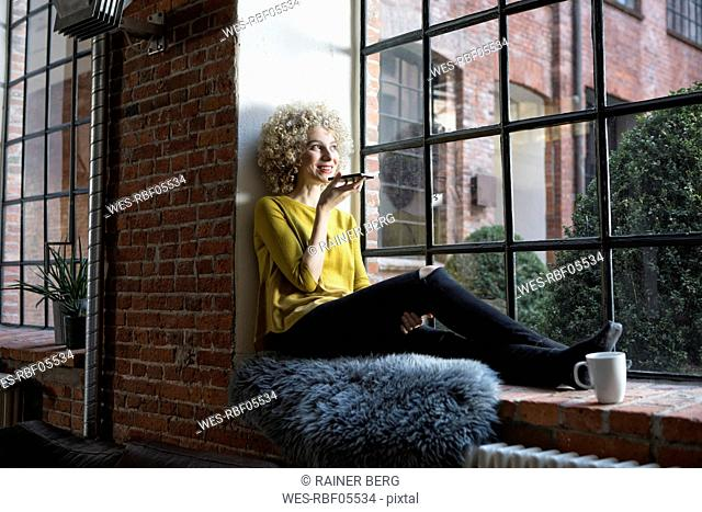 Young woman sitting on window sill, speaking into smart phone