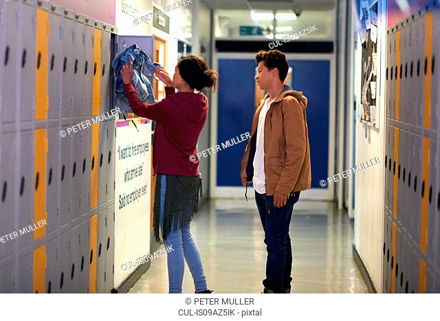 Young female student removing jacket from college locker