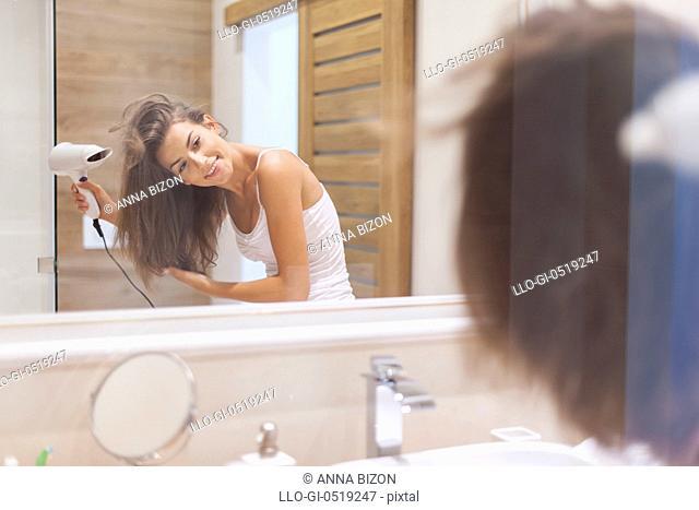 Happy woman drying her hair in bathroom. Photo taken through glass. Debica, Poland