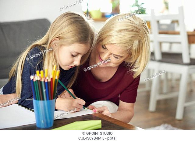 Grandmother helping granddaughter with homework at home