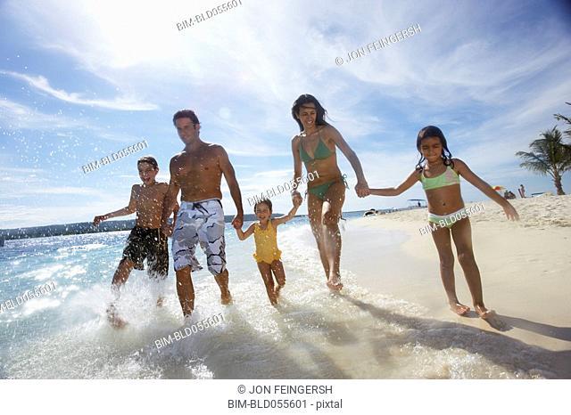 Hispanic family running in ocean surf