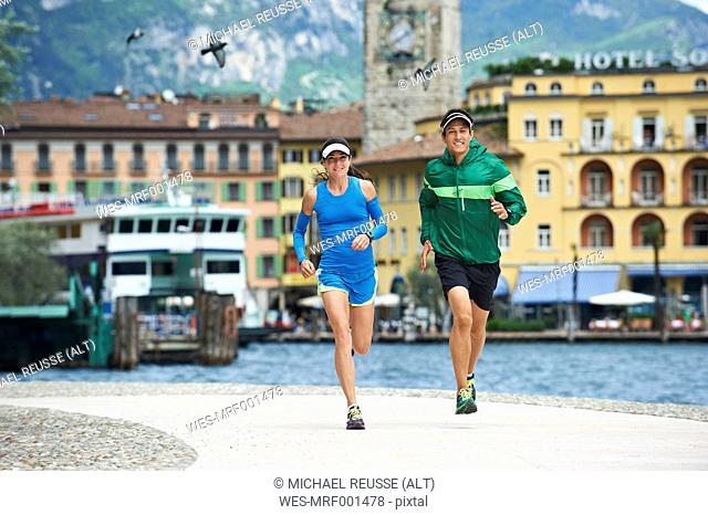 Italy, Trentino, couple running at Lake Garda
