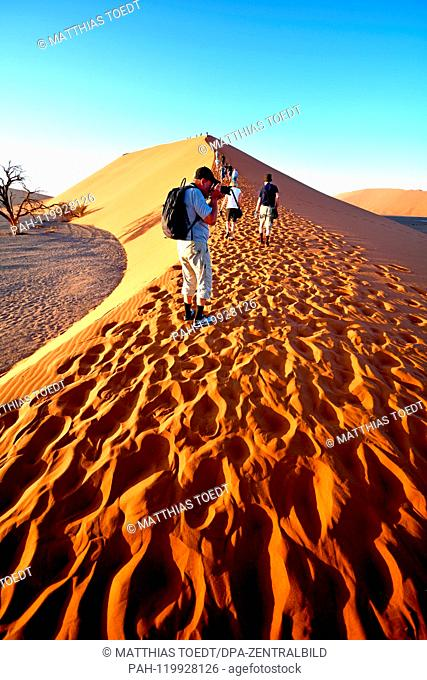 Tourists take photos of the ascent on a ridge in the Sossusvlei, the crowd of visitors completely crushed the natural sand structure, taken on 01.03