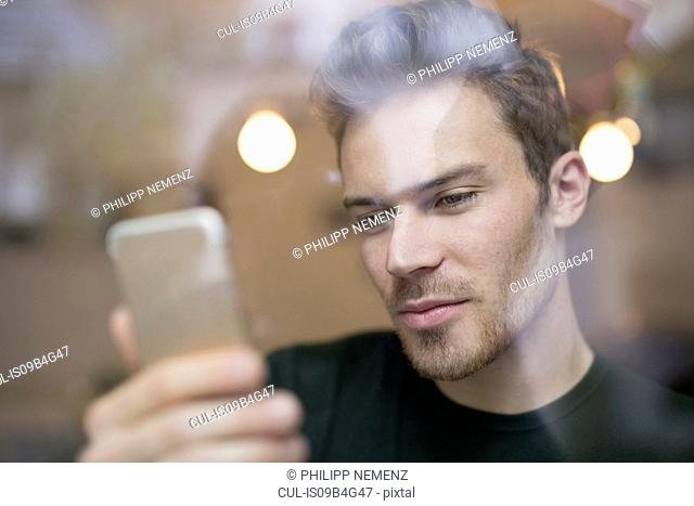 Cafe window view of mid adult man looking at smartphone