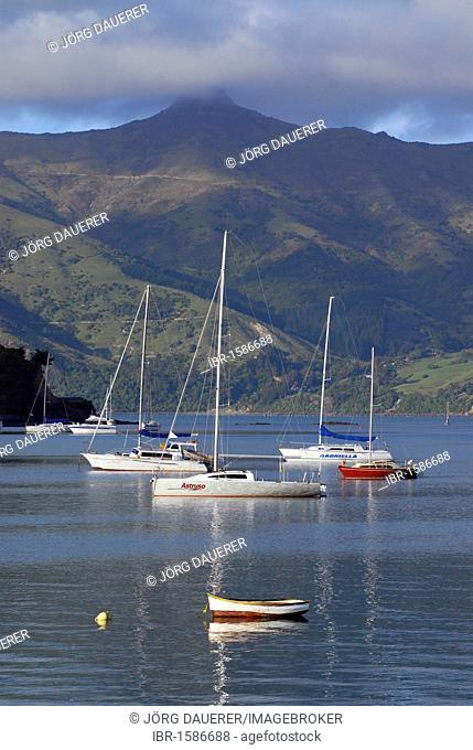 Boats in Akaroa Harbor and fog over the hills of Banks Peninsula, Canterbury region, South Island, New Zealand
