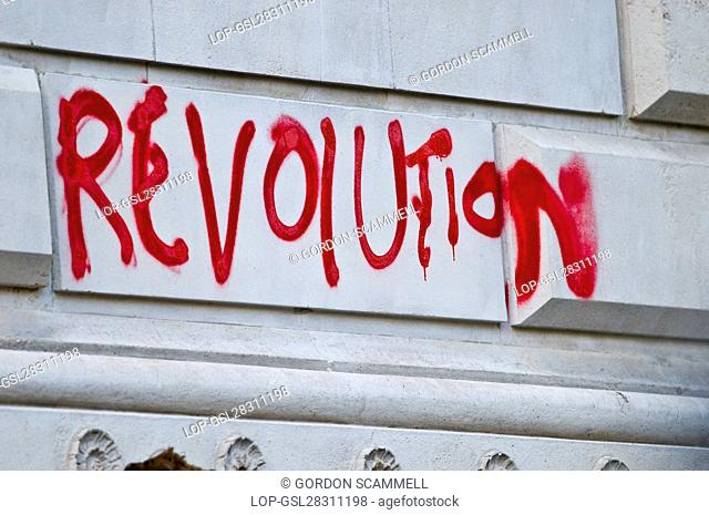 England, London. 'Revolution' written in red spray paint on a wall