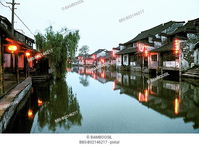 Illuminated houses by river at dusk, Xitang Town, Jiashan County, Jiaxing City, Zhejiang Province of People's Republic of China