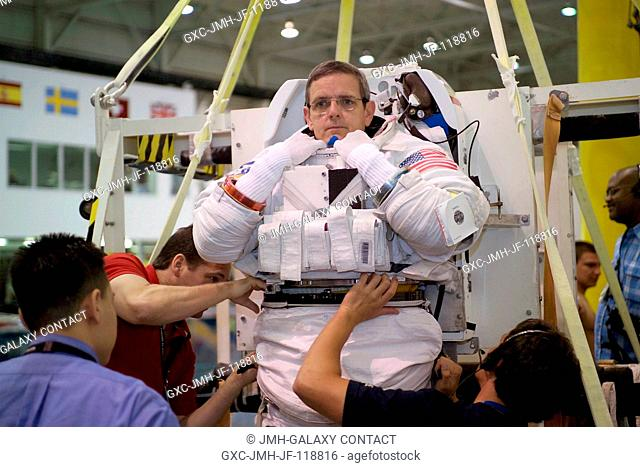 Astronaut William S. McArthur, Jr., Expedition 12 commander and NASA Space Station science officer, dons a training version of the Extravehicular Mobility Unit...