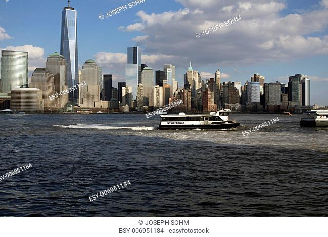 From New Jersey, a water taxi is seen in front of New York City Skyline featuring One World Trade Center (1WTC), Freedom Tower, New York City, New York, USA