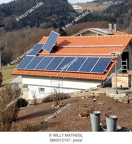 worker installing solar panels on tiled roof, Bavaria, Germany, Europe