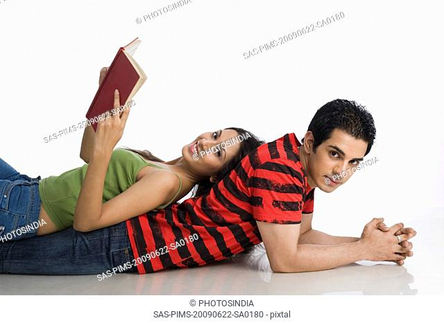 Woman lying on a man's back and holding a book