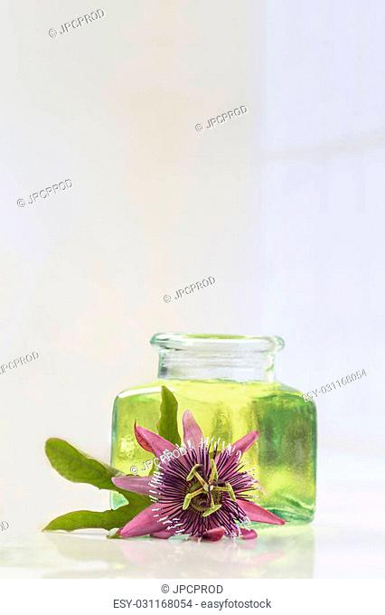 Passion flower essential oil blue glass bottle, isolated over white background. Passiflora