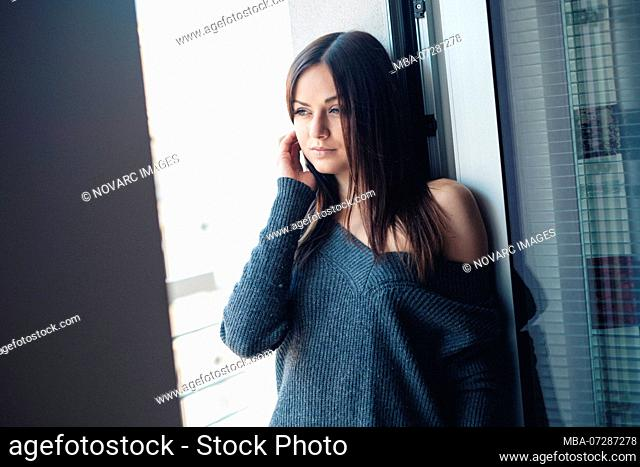 Woman in underwear stands at a window