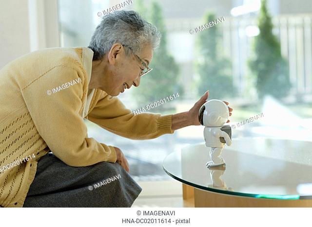 Senior woman playing with robot