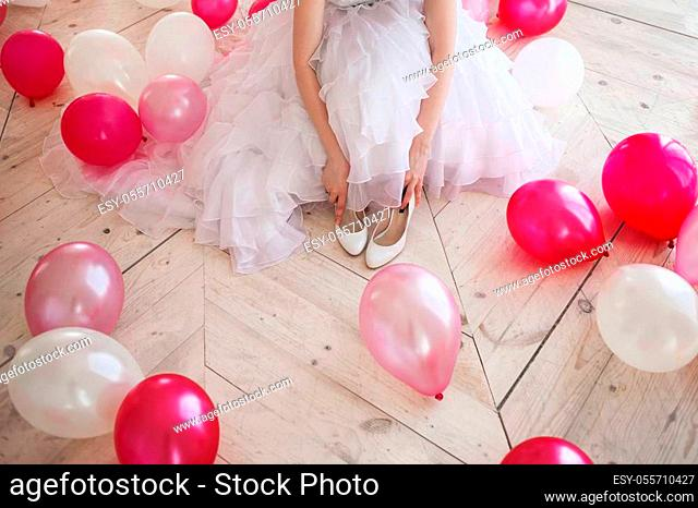 Young woman in wedding dress in luxury interior with a mass of pink and white balloons, sitting on the floor