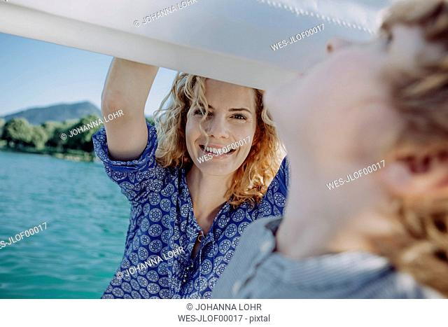 Smiling mother looking at son on a sailing boat
