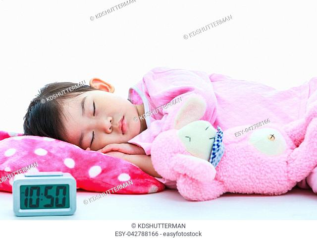 Healthy children concept. Asian child with doll sleeping peacefully. Adorable girl in pink pajamas sleep tight with alarm clock in foreground