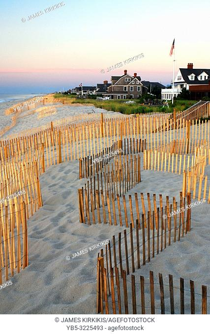 Snow fences zip zag along the sand dunes in front of large summer homes