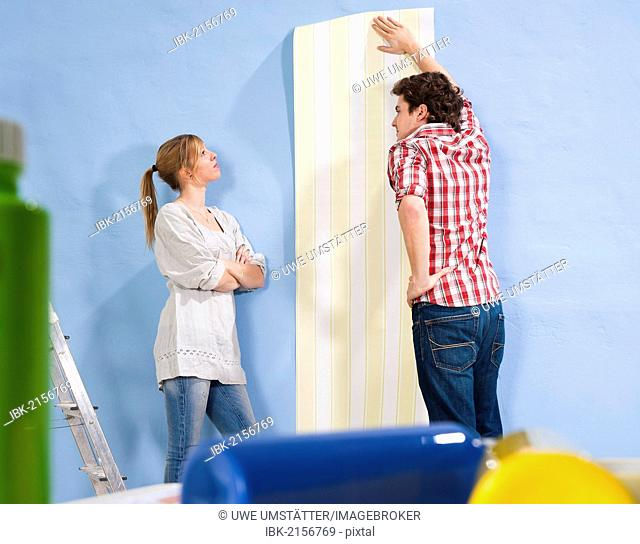 Young couple applying wallpaper to a wall