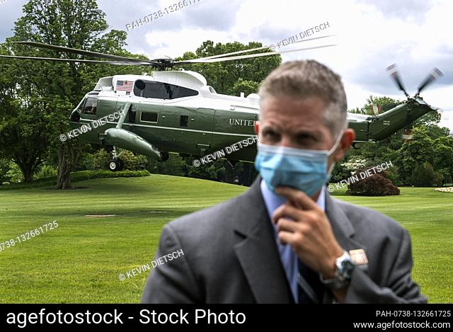 A Secret Service agent wears a mask as he watches President Donald Trump and First Lady Melania Trump depart the White House in Washington, DC on Wednesday
