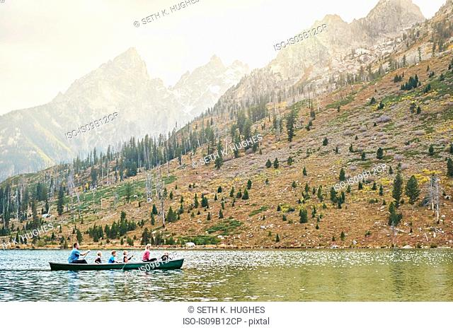 Family with four children paddling canoe on lake, Grand Teton National Park, Wyoming, USA