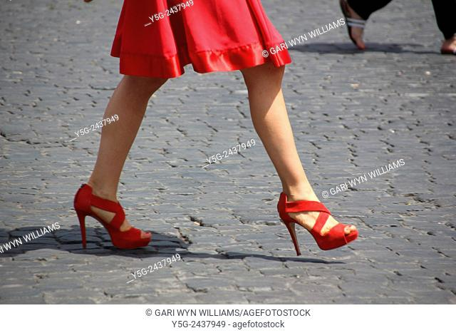 A woman with red dress and shoes walking in piazza del popolo square in Rome Italy