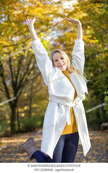 Pretty blonde young woman walking in Park and smiling at camera with arms raised